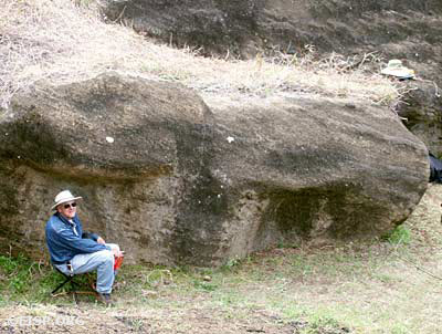 EISP field crewmember Gordon Hull sitting alongside Moai RR-03C-011, which is still attached to the bedrock, Rano Raraku Interior Quarry, 2002.