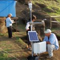 Conservation scientist Christian Fischer downloading data from environmental monitoring equipment. Moai 157 has already been covered to protect it from the elements.  Monica Bahamondez P. and Jo Anne Van Tilburg in background.